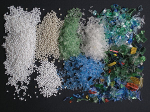 Dvě podoby polyethylentereftalátu (PET), suroviny pro výrobu PET lahví. Vlevo granulát (panenský PET), vpravo recyklát z použitých PET lahví v podobě drti a vloček.