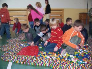 Školáci ze základní školy v Buštěhradě skládají z barevných víček od PET lahví mapu České republiky.
